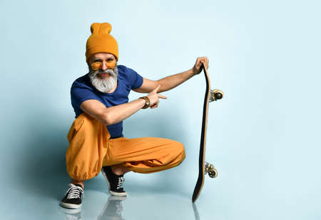 A gray-haired man in a T-shirt, sunglasses, orange pants and a hat, sneakers, bracelets. Looking to the side, holding a black skateboard, squatting against a blue background. Fashion, style, sports.