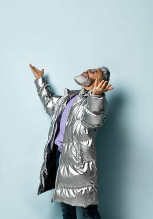 gray-haired, bearded, elderly grandfather in a purple pullover and sunglasses, a silver down jacket, jeans. He raised his hands and, looking up, poses against a blue background. Close up, copy space