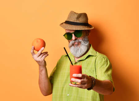 aged man in hat, green shirt, sunglasses. He is smiling, holding an orange and glass of fresh squeezed juice with black tube, posing on orange studio background. Close up, copy space