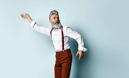 gray-haired bearded man in a white shirt, brown pants and suspenders. He tries to run away, looks around, raises his hand, poses against a blue background. Fashion and Style. Full length, copy space 免版税图像