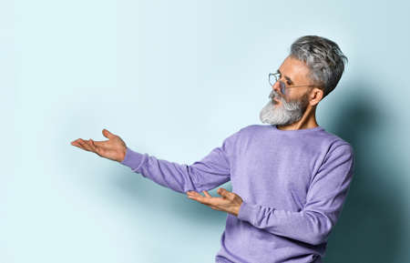 gray-haired, bearded, elderly man in sunglasses and a purple sweater. Shows something with his hands and looks at it, posing against a blue background. Fashion and Style. Close up, copy space