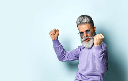 Gray-haired, bearded, aged man in sunglasses and purple sweater. He is dancing with clenched fist while posing against blue studio background. Fashion and style. Close up, copy space