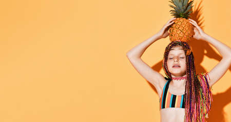 Teenage girl with african pigtails, golden jewelry on head, in colorful swimwear. She closed her eyes, holding pineapple on head, posing on yellow background. Childhood, summer. Close up, copy space