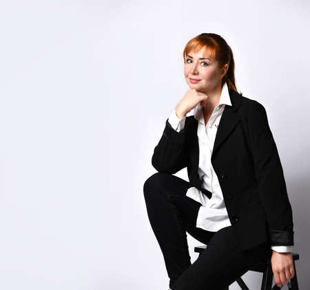 Young elegant red-haired business woman in formal suit sitting on a chair against a white wall. Smiling successful lady touching collar with hand looking to the side. Studio vertical portrait shot