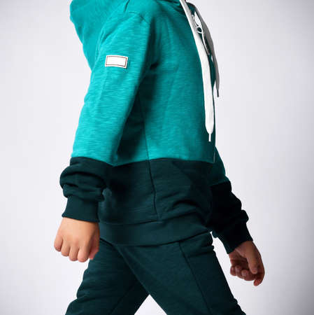 Close up side view of little child hands in sports suit on gray background. Details of clothes for boys, green sports suit for a school student. Children fashion concept.