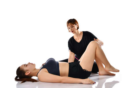 girl trains with a personal instructor, does gymnastics lying on the floor on her back. Female breathing control coach. Yoga, pilates, postpartum gymnastics concept. Studio shot on white background
