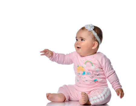 girl in a pink suit looks to the side on a white background in the studio. A surprised child sits on the floor and looks at something with interest. Space for text or promotional items.