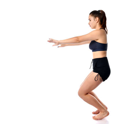 Studio portrait of confident healthy sporty athletic woman squatting doing sit-ups isolated over white background copy space. Workout, exercise, fitness, yoga exercise. Post-natal gymnastics