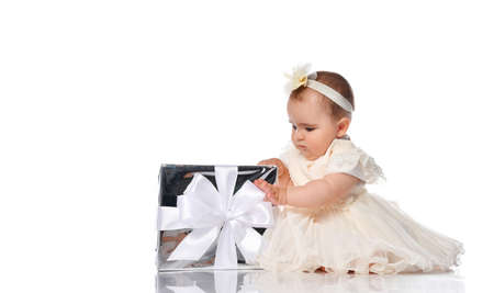 Focused child girl with interest unfolds a holiday gift on a white background. Girl dressed in a beige dress cheats barefoot on the floor in the studio. Baby gifts concept. 免版税图像