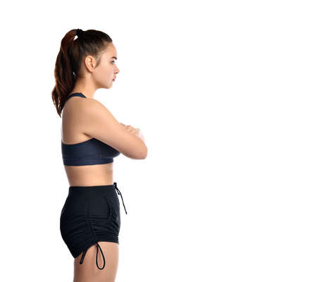 Attractive sporty female of European appearance folded her arms and is going to squat on a white background. Focused woman dressed in a sports top and training shorts. Place for text. View in profile.