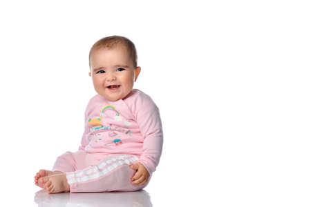 Cute little girl laughs looking at the camera on a white background. Girl dressed in pink pajamas posing sitting on the floor in the studio. Place for text or promotional products.