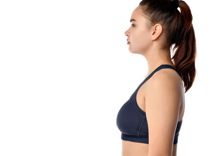 Side view of a young athletic woman with a ponytail hairstyle, wearing a sports top on a white background. Woman doing neck exercises, looking to the side