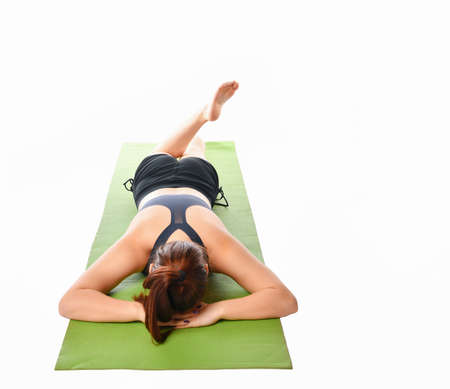 Brunette woman in a sports uniform who practices yoga relaxed lying on the mat face down with folded arms under his head on a white background. Concept of weakness after strength training. 免版税图像