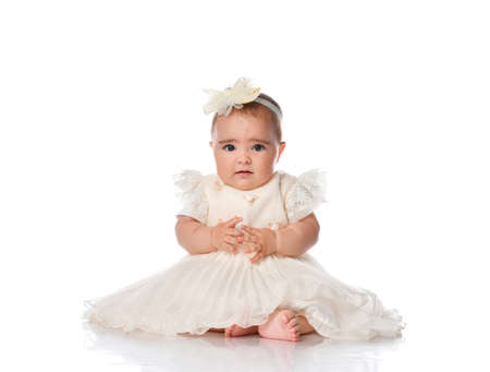 Beautiful child girl in a festive dress and a hair band sitting on the floor. Toddler toddler looking at camera studio portrait shot on white background. Children's fashion and beauty