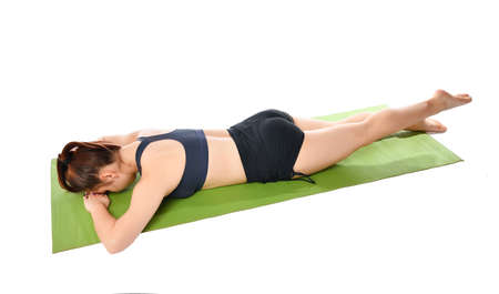 Athletic brunette woman in a dark uniform lies face down on a sports mat and does an exercise to stretch her legs. Girl in dark light sportswear puts her hands under her head and stretches her leg.