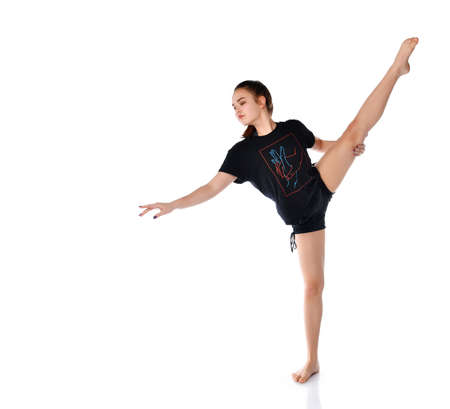 Flexible sports girl performs dance elements on a white background in the studio. Brunette girl in dark clothes performs acrobatic elements. Rhythmic gymnastics concept. Place for text.