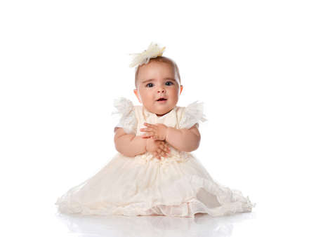 Beautiful baby girl in princess dress sitting on floor with arms folded on chest. Toddler with surprise emotion on face studio portrait full length shot on white background. One year birthday concept