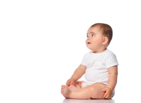 Adorable little baby girl smiling, sitting on the floor, studio shot, isolated on white background, lovely baby portrait 免版税图像