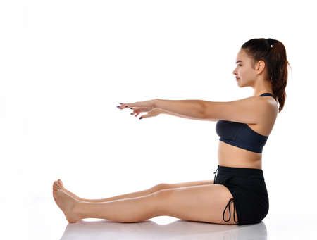 Female athlete dressed in a sports uniform sits sideways on a white background with outstretched arms and legs. Woman performs sports exercises and balance exercises. Place for text. 免版税图像