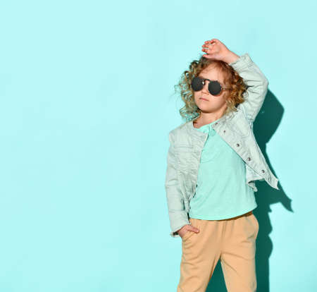 Stylish blond girl with curly hair in glasses with a black lens, stands thoughtfully holding one hand in her pocket, touching the neck of the other, isolated on turquoise. Childhood, casual stylish clothes.