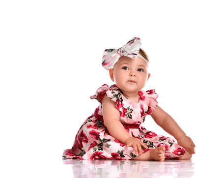 Serious little baby girl with pretty coiffure decorated bow headband wearing beautiful multicolored dress sitting on floor posing for camera. Isolated studio shot on white background