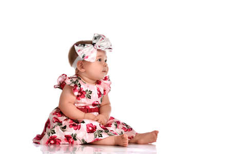 Girl in a dress and a headband sitting barefoot on a white background. A girl in a pink dress with flowers and a bow on her head sits barefoot with a cute expressive face and looks up.