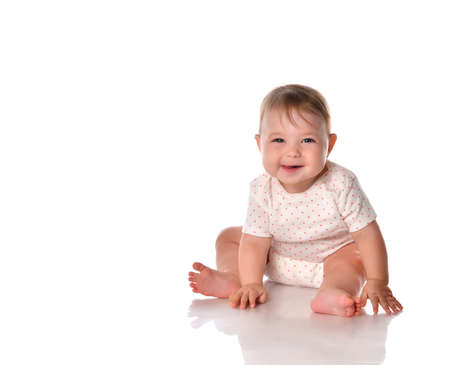 Happy child laughing portrait. Female toddler with positive emotions on her face sitting on the white studio floor. Little adorable baby looking at the camera. Excited Caucasian Newborn Shot on
