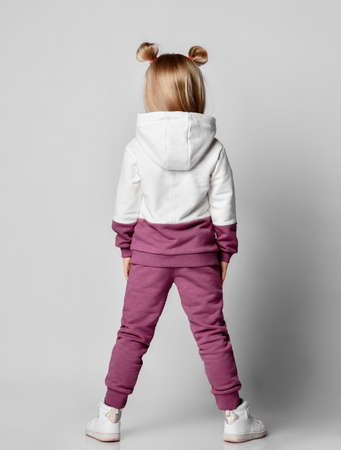 little girl in a colorful tracksuit stands with her back to the camera, demonstrates shopping on a gray background. Kids athletes, active lifestyle, stylish sportswear.