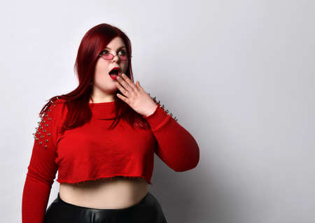 Large red-haired girl in a red studded top, black leather skirt, sunglasses. She covered her mouth with her hands and looked scared, imagining herself isolated on white. Fashion Style. Close copy space