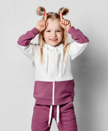 Little funny girl with a charming smile and hairstyle puts her fingers to her head on a gray background. Child poses in a colorful fashionable sports suit. Children athletes and stylish sportswear.