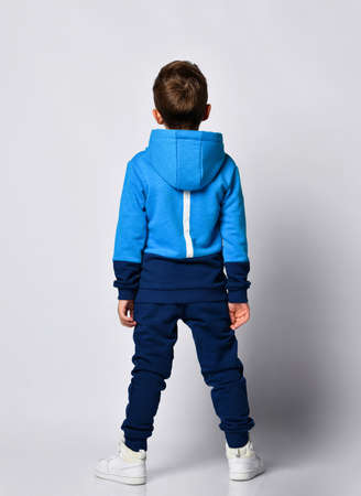Fashion boy posing wearing warm blue black sports tracksuit and snickers. Full length isolated studio portrait on gray background back view. Child sport clothing shop promotion 免版税图像