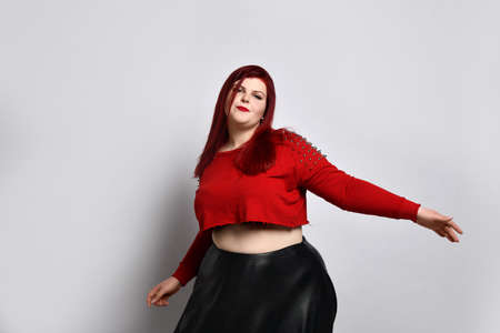 plump ginger in a red top with spikes, a bra with a red top and a leather skirt, earrings. She is dancing and singing, posing on a white background photo. The concept of fashion and style. Close copy space