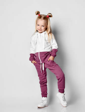 Little blonde girl with a sly smile, dressed in a trendy tracksuit, posing against a gray background. Child poses, holding hands in pockets. Advertising of children's fashion.