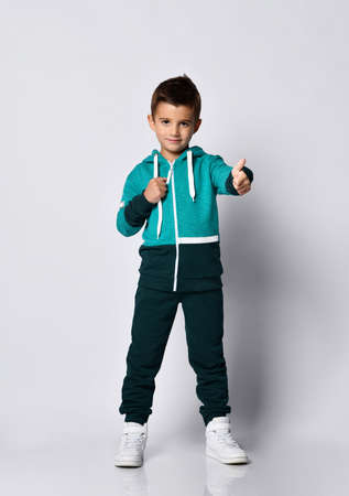 Boy in sportswear gesturing thumbs-up portrait. Little schoolboy in black green hoodie tracksuit showing like sign gesture isolated on grey studio background. Childhood, fashion, advertising, sport 免版税图像