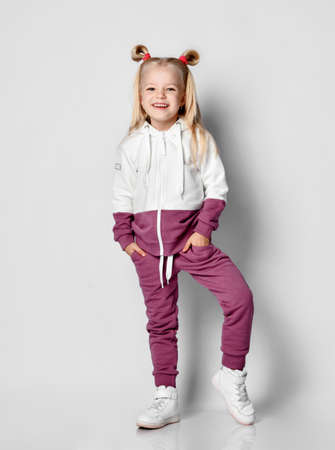 Little blonde girl with a sly smile dressed in a fashionable sports suit posing on a gray background. Child poses holding his hands in his pockets. Childhood fashion advertising.
