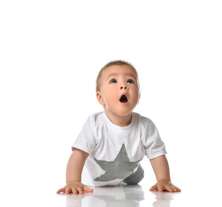 small surprised toddler child crawls towards the camera and saw something interesting above. happy childhood. care