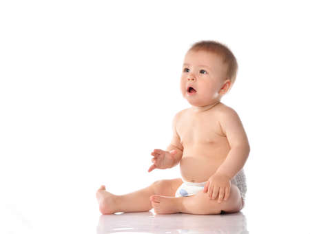 little baby in a diaper claps his hands while sitting on the floor. An agitated baby with surprise on his face, clasped his palms together, applause. Studio portrait isolated on white