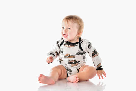 Close up portrait of a happy blonde baby with blue eyes boy on a white background. Boy, dressed in a stylish modern bodysuit with funny raccoons, sits barefoot on the floor and laughs out loud.