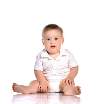 Portrait of a concerned child sitting in the studio on a white background. Little boy dressed in a white bodysuit looks with interest at the camera with his mouth open.