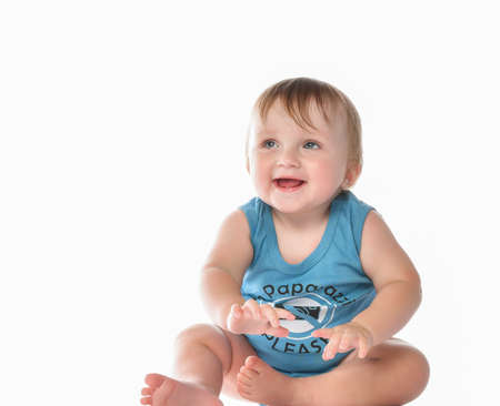little cute toddler in blue bodysuit sits on a white studio background and looks to the side