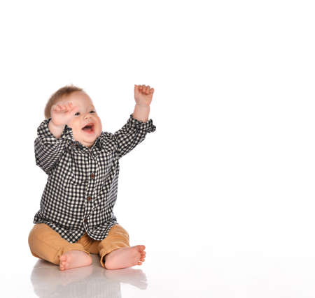 little boy in a black and white plaid shirt and beige pants raises his hands up and smiles directly into the camera in the studio on a white background. Child development concept