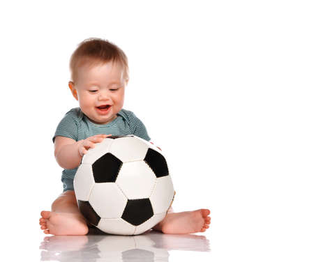 Little kid boy dressed in a striped green bodysuit holding a soccer ball and going to sneeze sitting barefoot on a white background. Active childhood concept.