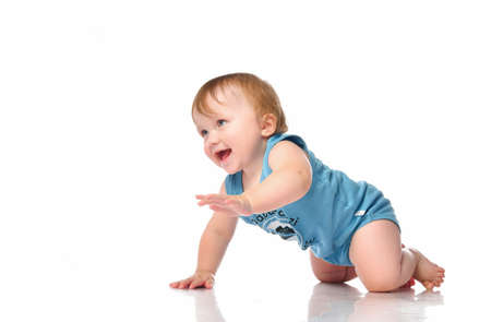 Infant baby boy crawling and looking happy at corner isolated on white background. A boy with blue eyes in a blue bodysuit is about to get on all fours and crawl. Banner. Place for your text. 免版税图像