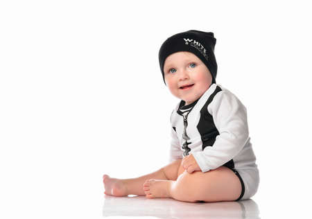 Happy smiling boy in trendy outfit studio shot portrait isolated on white background with shadow. Male toddler in casual jumpsuit and hat. looking away