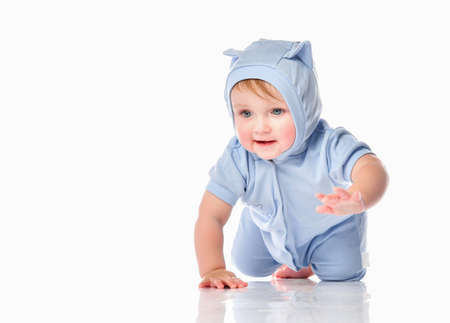 cute little kid in a funny blue suit and a hood with ears on his head, crawling towards the camera on the studio white floor. Full-length portrait. Toddler activities and development
