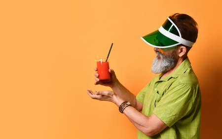 man in a green sun visor, shirt, sunglasses. He smiles, holds a glass of freshly squeezed juice with a slice of lemon and a straw, clenched his fist, posing against an orange background. Standard-Bild