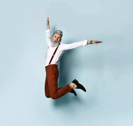 Stylish gray-haired jumper man in stylish clothes jumping on a blue background. Youth and old age concept