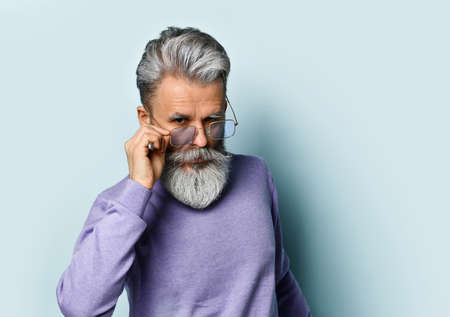 He adjusts his sunglasses and looks at you, posing against a blue studio background. A gray-haired, bearded, elderly man in a purple sweater. Fashion and Style. Close up, copy space