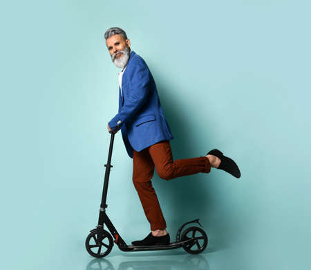 gray-bearded elderly man in a white shirt, jacket, brown pants and moccasins. He rides a black scooter, posing sideways on a blue background. Fashion, style, sports. Full length, copy space
