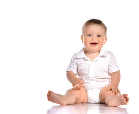 Portrait of infant child baby boy toddler with dark blue eyes dressed in a white bodysuit. Child sits barefoot and happily smiles on a white background with space for text.